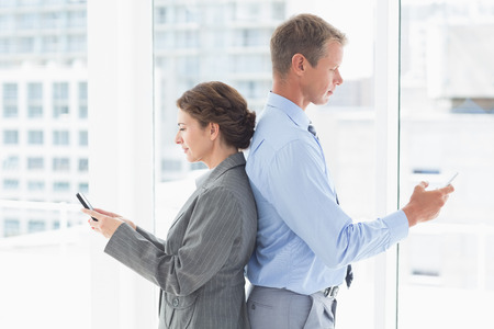 colleague: Businesswoman back-to-back with colleague in an office