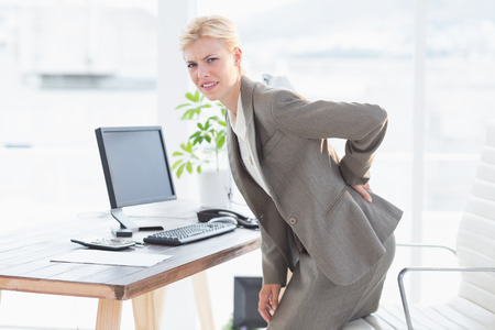woman back pain: Sad businesswoman having back pain in her office Stock Photo