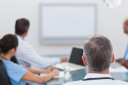 staff meeting: Doctors looking at white board in meeting