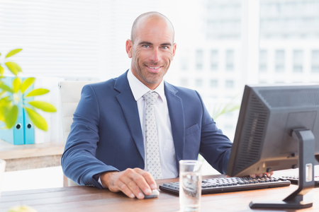 businessman smiling: Smiling businessman looking at camera in his office