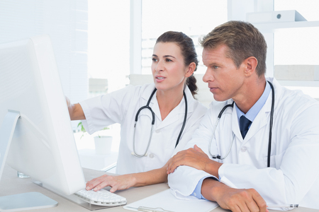 medical doctors: Concentrated doctors using computer in medical office