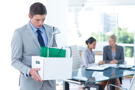 well laid: Businessman carrying his belongings in box after being fired Stock Photo
