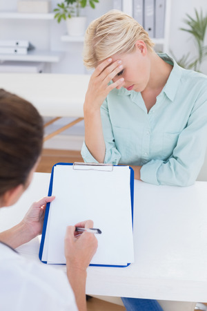 head ache: Patient with head ache ache speaking with her doctor in medical office