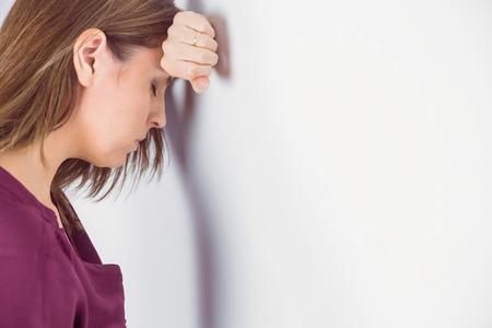 desolaci�n: el hombre deprimido que inclina su cabeza contra una pared en el fondo blanco Foto de archivo