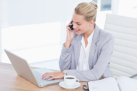 phoning: Smiling businessman phoning at her desk while she using her computer  in her office Stock Photo