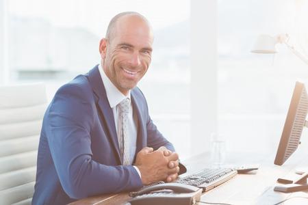 monitor de computadora: Sonriente hombre de negocios mirando a la c�mara en su oficina Foto de archivo