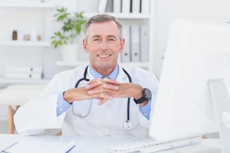 Sourire médecin regardant la caméra avec les mains croisées dans le cabinet médical