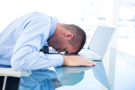 tired businessman: Tired businessman resting on laptop in an office