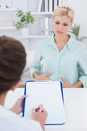 desolaci�n: Patient with stomach ache speaking with her doctor in medical office Foto de archivo