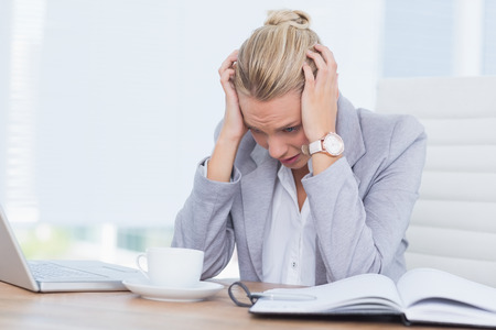 pounding head: Frowning woman grasping her head in her office