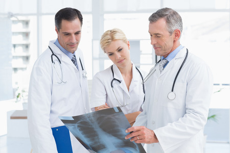 medical doctors: Concentrated doctors looking at Xray in medical office Stock Photo