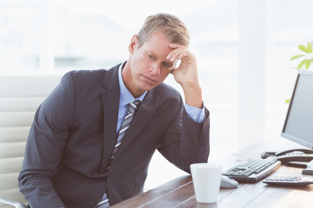 unhappy worker: Businessman with his hand on his forehead in his office