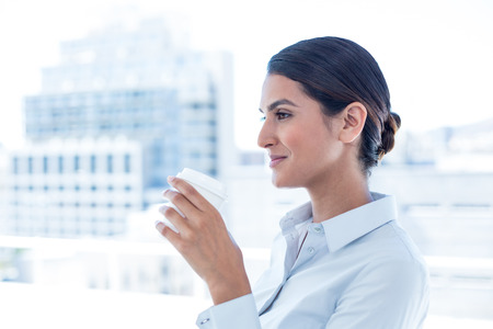 disposable cup: Smiling businesswoman holding disposable cup in an office