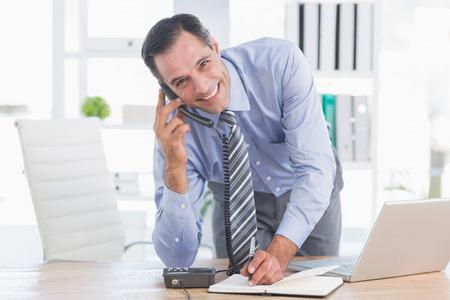 phoning: Smiling businessman phoning at his desk