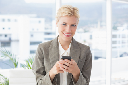 blonde females: Businesswoman looking at camera and using her smartphone in an office
