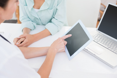 tablet: Doctor using tablet pc with her patient in medical office