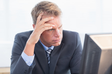 male headache: Businessman with his hand on his forehead in his office