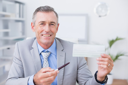 cheque: Smiling businessman holding cheque in his office Stock Photo