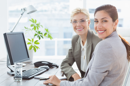 young business people: Smiling businesswomen looking at camera and working together in an office