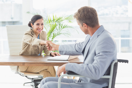 equal opportunity: Businesswoman shaking hands with disabled colleague in an office Stock Photo