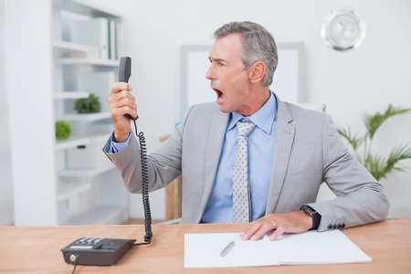 answering phone: Irritated businessman answering phone in his office