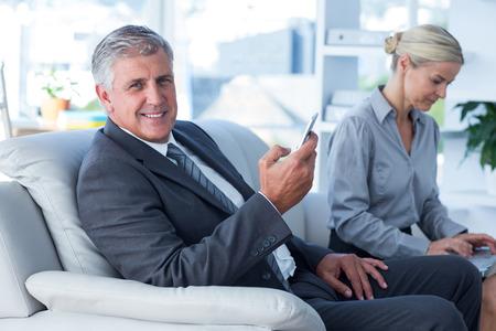 SECRETARIA: Sonriente hombre de negocios en la llamada mientras su secretaria mira port�til en la oficina Foto de archivo