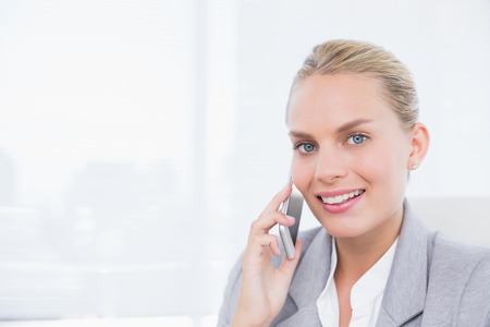 phoning: Smiling businessman phoning at her desk in her office
