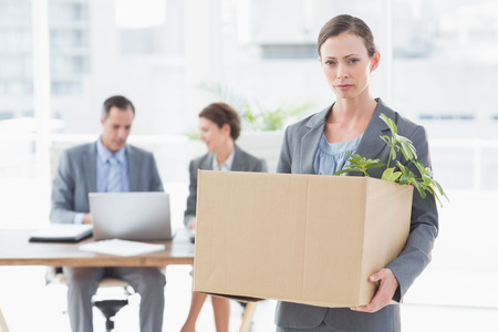 well laid: Businesswoman leaving office after being fired and carrying her belongings