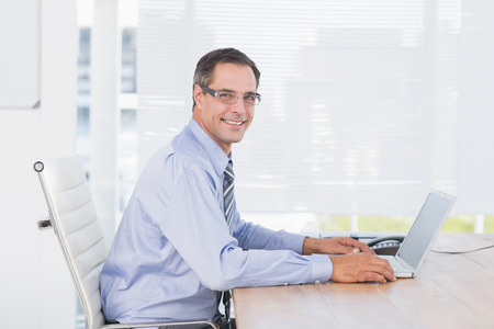 businessman smiling: Smiling businessman using his computer in his office Stock Photo