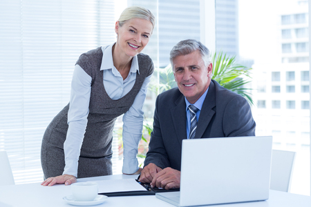 to the secretary: Smiling businessman with secretary checking diary in an office Stock Photo