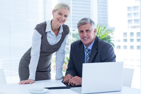 secretaria: Sonriente hombre de negocios con la secretaria diario de comprobación en una oficina