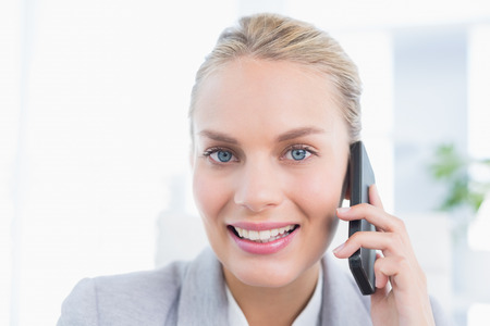Smiling businessman phoning at her desk in her office