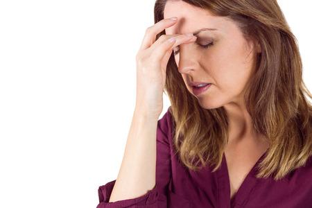 dolor de cabeza: Brunette bonito con dolor de cabeza tocando su frente sobre fondo blanco Foto de archivo