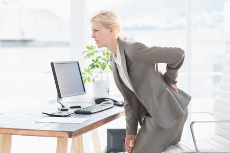 hand on hip: Sad businesswoman having back pain in her office Stock Photo