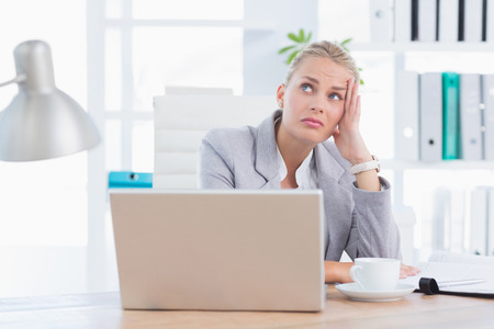 distress: Frustrated businesswoman with head in hand in her office