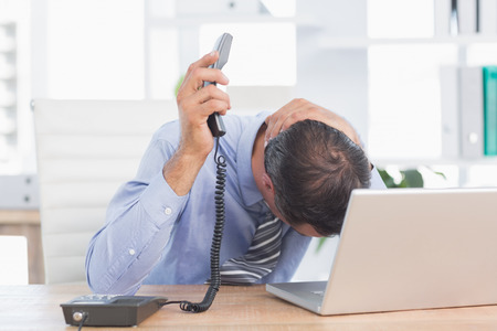 Frustrated businessman phoning at his desk in his office Stock Photo
