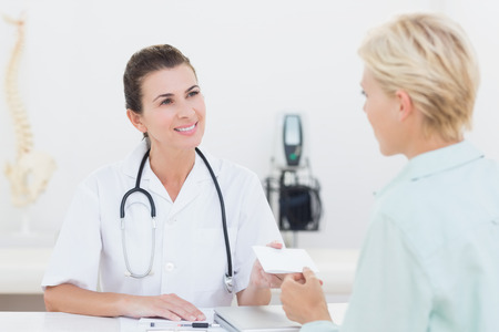 cheque: Patient giving cheque to her doctor in medical office Stock Photo
