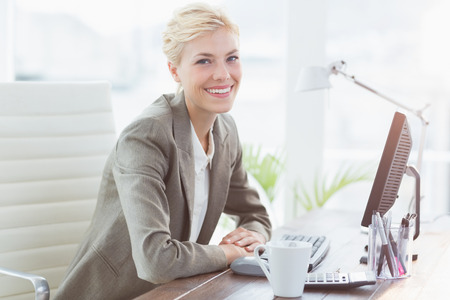 elegant woman: Smiling businesswoman looking at camera in her office Stock Photo