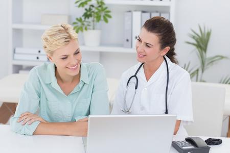 doctoras: Paciente y m�dico que mira el ordenador en la oficina m�dica