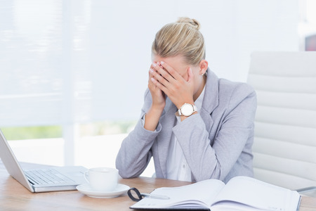 Frowning businesswoman grasping her head in her office