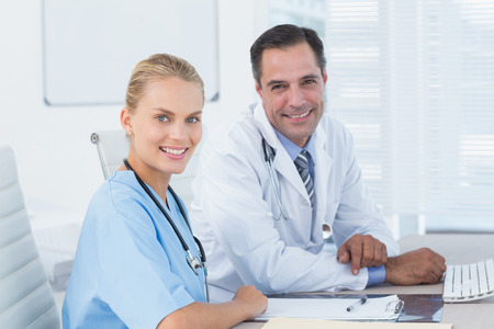 Smiling doctor and nurse looking at camera in medical office