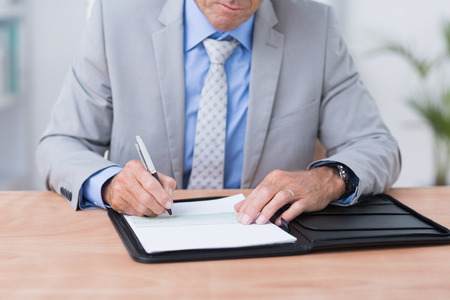 Scrittura dell'uomo d'affari su un documento nel suo ufficio