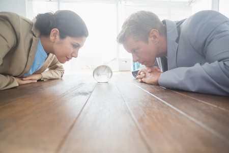 silhouette feminine: Business partners watching crystal ball in an office