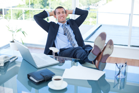 swivel chair: Businessman relaxing in a swivel chair in his office
