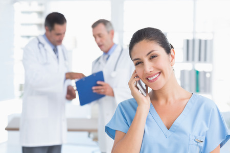 phoning: Nurse phoning while her colleagues working in medical office