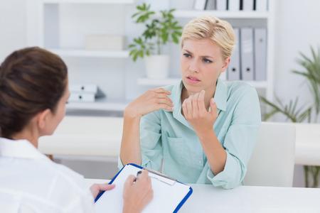 desolaci�n: Habla paciente Descontento con el m�dico en el consultorio m�dico Foto de archivo