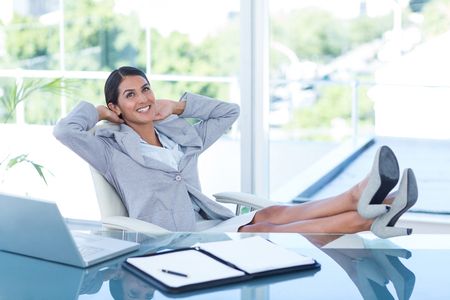 swivel chair: Businesswoman relaxing in a swivel chair in her office