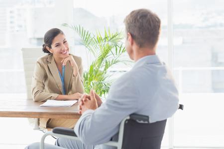 personas discapacitadas: Empresaria sonriente entrevistar candidatos con discapacidad en una oficina