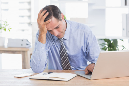 frustrate: Frustrated businessman working in his office at work Stock Photo