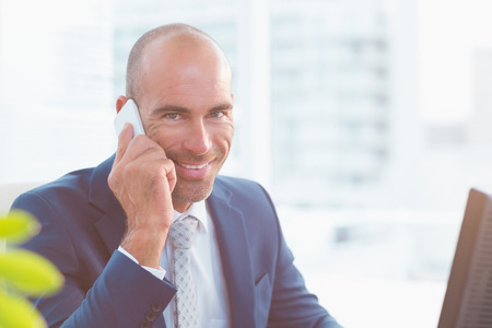 Smiling businessman looking at camera and calling in his office